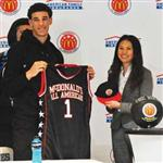 Male high school basketball player receiving jersey from a female adult